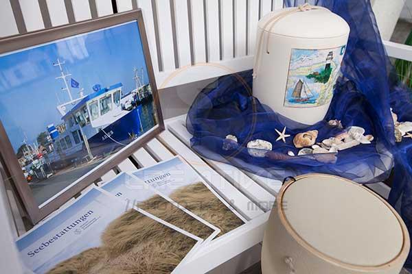 Auslage mit Infomaterial und Bildern einer Seebestattung bei Bestattungen Hörner